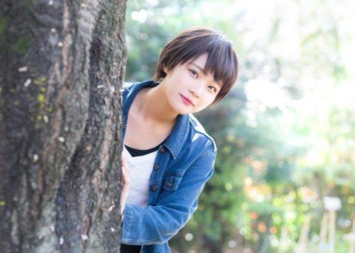 木の陰から顔を覗かせる女性