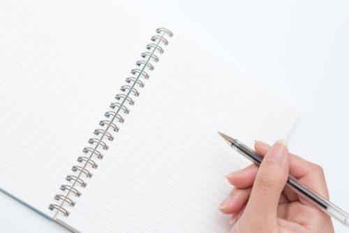 真っ白なノートにペンを持つ指