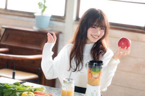 笑顔で林檎を持っている女性