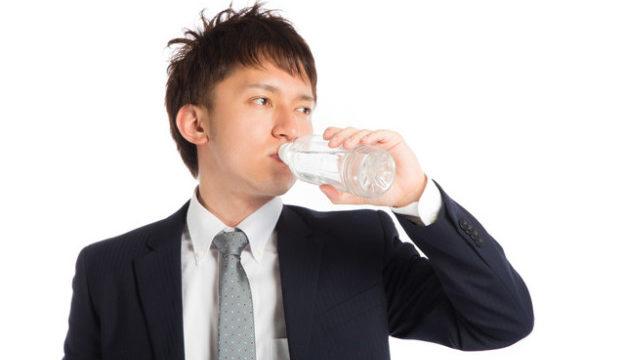 ペットボトルの水で喉を潤すサラリーマン