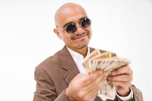 お金を数えて喜んでいるサングラスの男