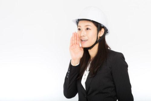 ヘルメットを被って声をかける女性社員
