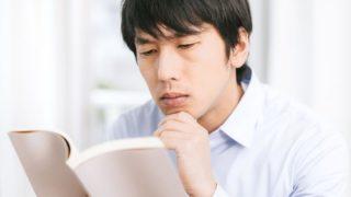 参考書を読みながら考える男性