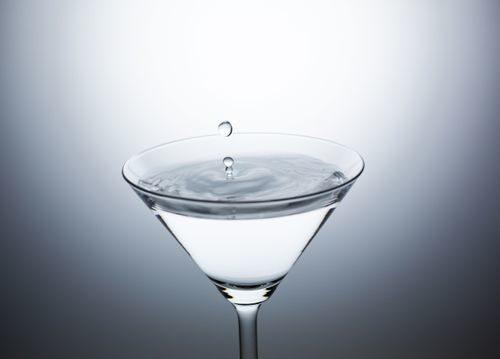 バーのカクテルグラスに落ちた水滴